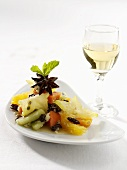 Exotic fruit salad on a platter with wine