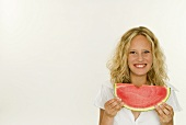 Blond woman holding a slice of watermelon in her hands