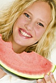 Blond woman eating a slice of watermelon