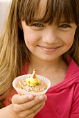 Small girl holding a muffin decorated with a marzipan hen