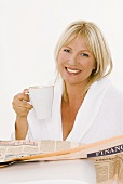 Blond woman with a cup of cappuccino reading newspaper