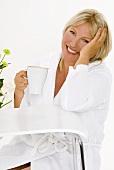 Blonde Frau sitzt mit einer Tasse Cappucchino am Tisch