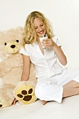 Young woman with glass of milk, sitting beside teddy bear