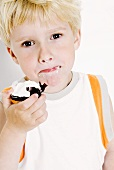 Small boy with a chocolate-covered marshmallow wafer