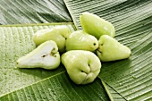 Green Java apples on banana leaves