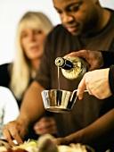 Olivenöl abmessen; zwei Menschen im Hintergrund