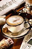 A cup of cappuccino amidst newspaper, keys and money
