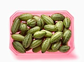 Baby cucumbers in a pink plastic tray
