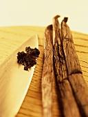 Vanilla pods and vanilla seeds on a knife