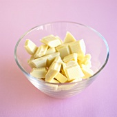 Broken white chocolate in a glass bowl