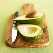 A halved avocado with knife on a wooden board