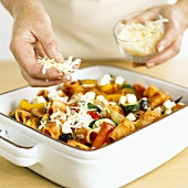 Sprinkling cheese over pasta and vegetable bake