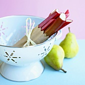 Rhubarb in a colander, pears beside it