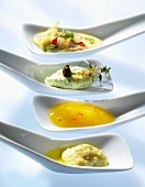 Four sauces and dips on small spoons