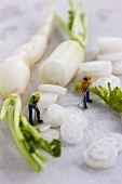 Two little toy men with white radishes
