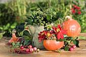 Herbstliche Deko mit Efeu, Kürbis, Dahlien und Zieräpfel