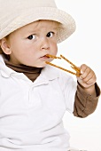 Small boy eating salted sticks