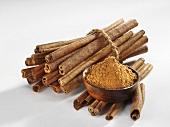 Cinnamon sticks and ground cinnamon in a small bowl