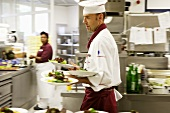Chef carrying several plates of salad