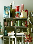 Various foods and utensils on kitchen shelf unit