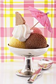 Neapolitan ice cream sundae with cream & cocktail umbrella