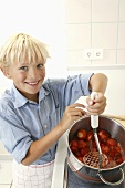 Blond boy crushing strawberries with a potato masher