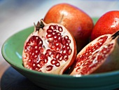 Two whole and one halved pomegranate in a dish
