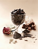 Coffee beans in a glass cup surrounded by chocolate & cinnamon