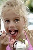 Blond girl eating a mixed ice cream sundae