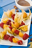 Skewered raspberries, physalis and kumquats
