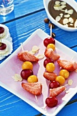 Skewered fruit with chocolate sauce and flaked almonds