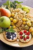 Bowl of fresh fruit with two berry tarts