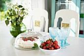Strawberry cream cake and bowl of fresh strawberries