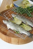 Preparing trout stuffed with herbs for grilling