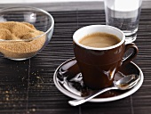 A cup of espresso with water and brown sugar