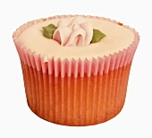 A cupcake with pink icing and sugar flower