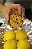 Hand hält eine geröstete Zitronenhälfte
