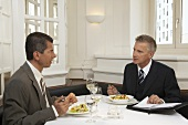 Two men having a meeting over a meal in a restaurant