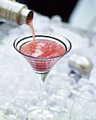Einen Cranberry-Cocktail eingiessen