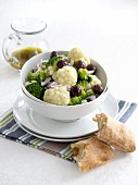 Cauliflower and broccoli salad with onions, olives and a dill dressing