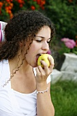 A young woman eating an apple