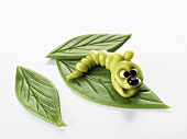 A marzipan caterpiller on marzipan leaves