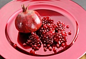 A pomegranate and pomegranate seeds on a red plate