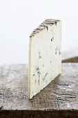A piece of blue cheese on a wooden board