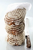 A stack of three loaves of bread with a cloth and a knife