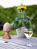 A glass of white wine, sun flowers and a terracotta ornament on a garden table