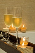 Two glasses of champagne and candles on a tray over a bath tub