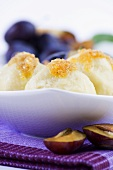 Potato dumplings with plums and buttered crumbs