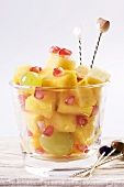 A fruit salad with pineapple, grapes and pomegranate seeds