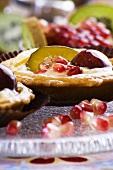 Fruit tartlets with kiwi, grape and pomegranate seeds